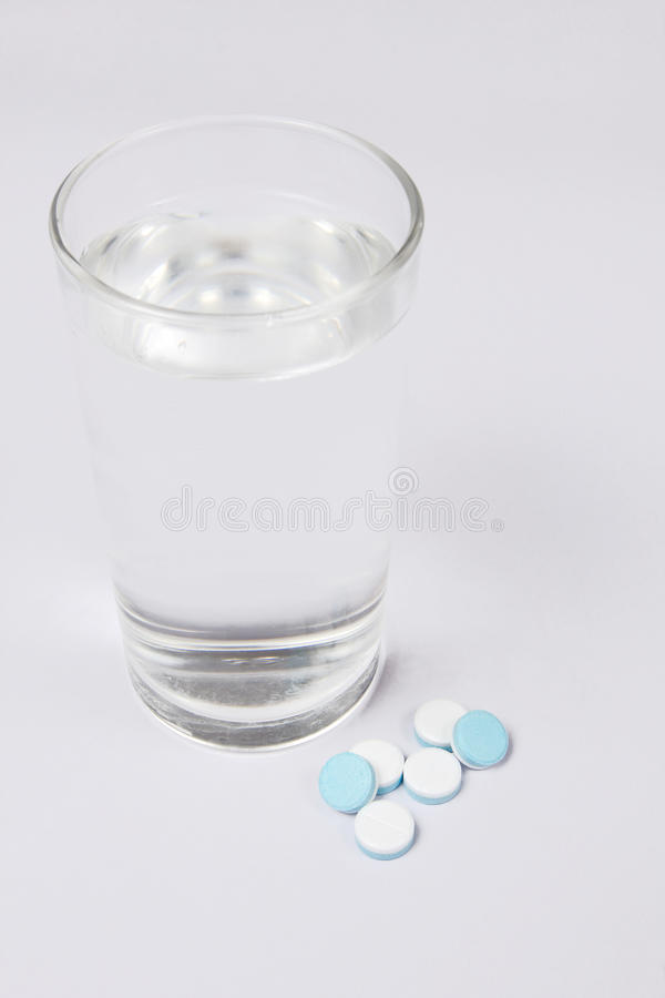 A glass of water and Pills, medicals, drugs, tablets in white. Unpacked stock photography