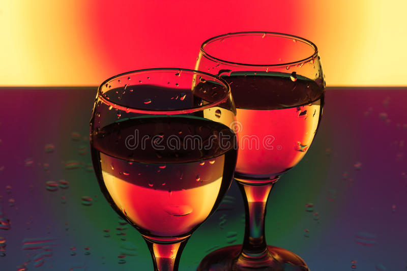 A glass of water on a red and yellow background royalty free stock photo