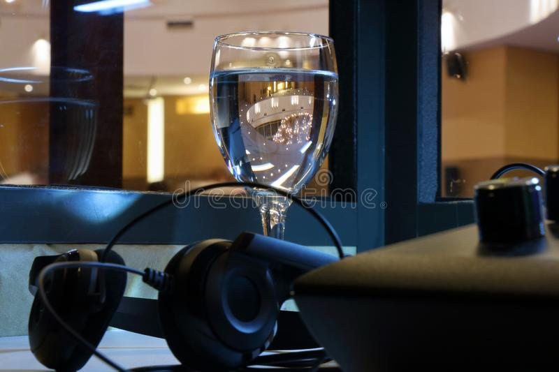 A glass of water for a simultaneous interpreter. A glass of water for the interpreter in a special cabin of simultaneous translation stock images