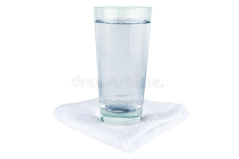 A glass of water stands on a towel.  stock image
