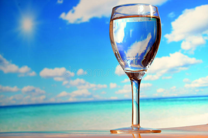 Glass of water in a sunny day. A glass of water at a sunny beach royalty free stock photography