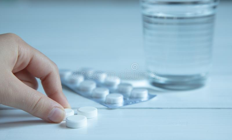 Glass with water and three white pills, vitamins on a white wooden table. Pills in packaging on the table. Fingers holding a pill royalty free stock photos