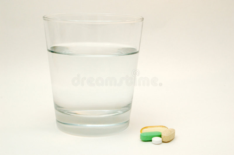 Glass Of Water and Vitamins. Glass Of Water and Daily Vitamins stock photography