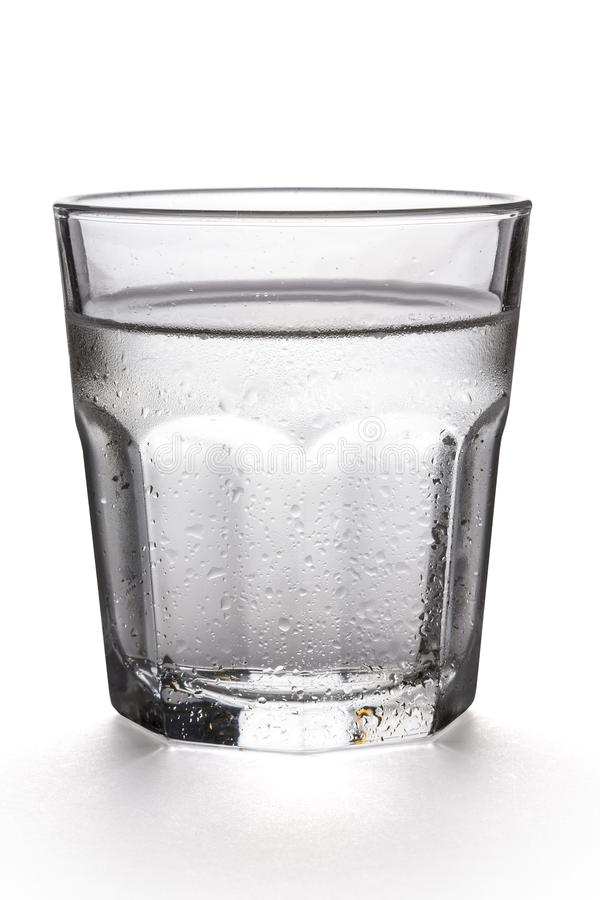 Glass of water on a white background. Glass of water on a white background, with a drop shadow, and condensation royalty free stock photo