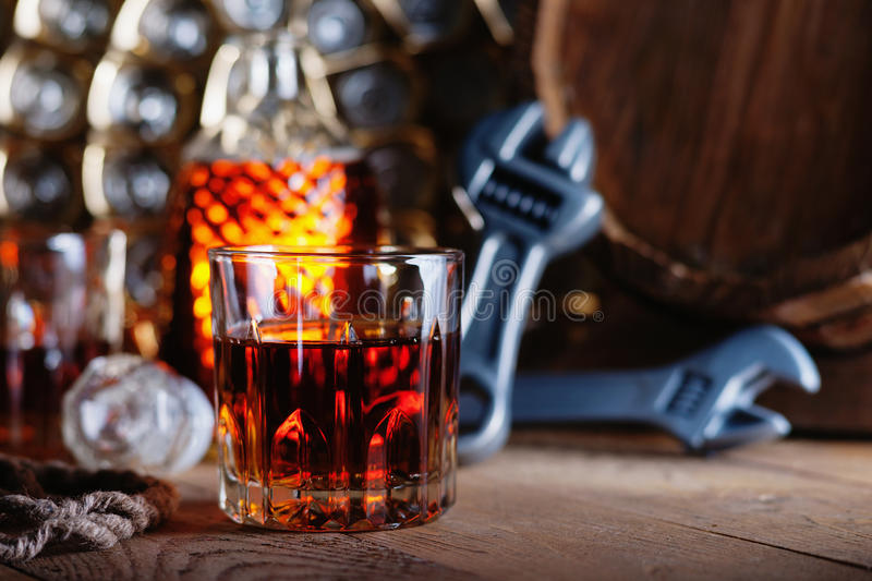 Glass of whiskey with adjustable wrenches and wooden barrel stock photos