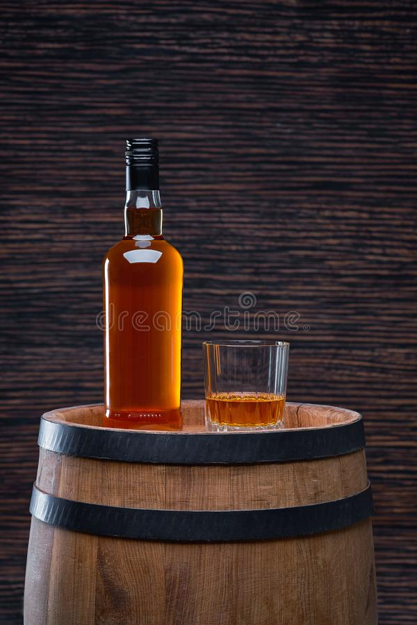 Whiskey glass and bottle on the old wooden table stock images