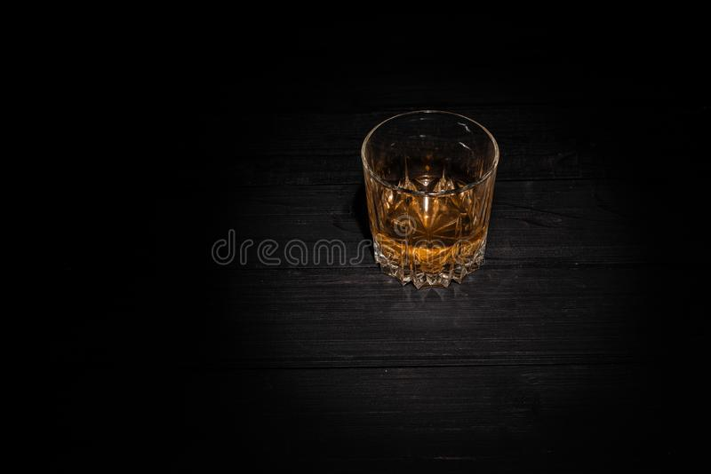 A glass of whiskey on a black wooden background. dark photo royalty free stock photos