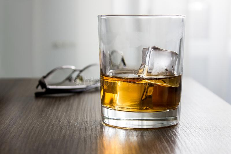 Glass of whiskey, brandy, cognac with ice cubes on wooden table desk with glassess. Mockup of product, gift for man.  royalty free stock images