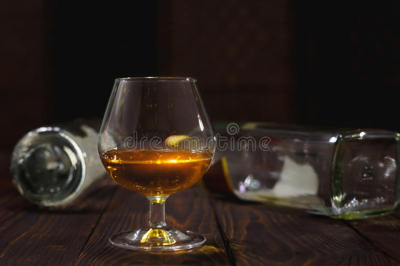 Glass of whiskey or brandy and empty bottles on wooden table royalty free stock photos