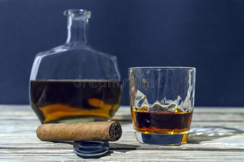 A glass of whiskey, a cigar with a guillotine and a bottle of alcohol are on the old textured light wooden table. stock photography