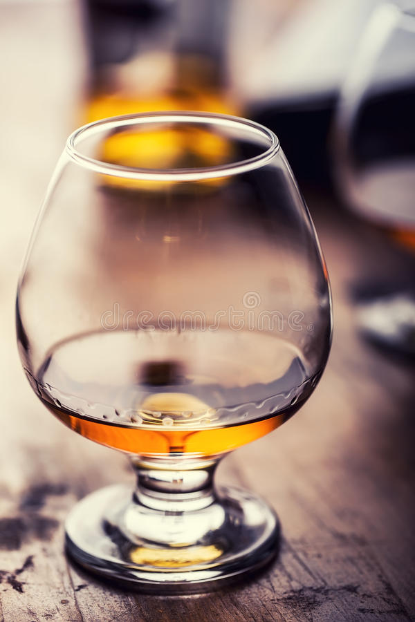 Glass whiskey cognac brandy or rum.One half full glasses of cognac on a wooden surface stock photo