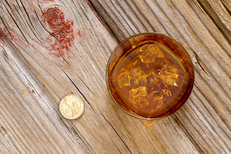Glass of whiskey and a coin on a bar counter. Glass of whiskey and a coin for a gratuity or tip standing on an old textured wooden bar counter, view from above royalty free stock photos