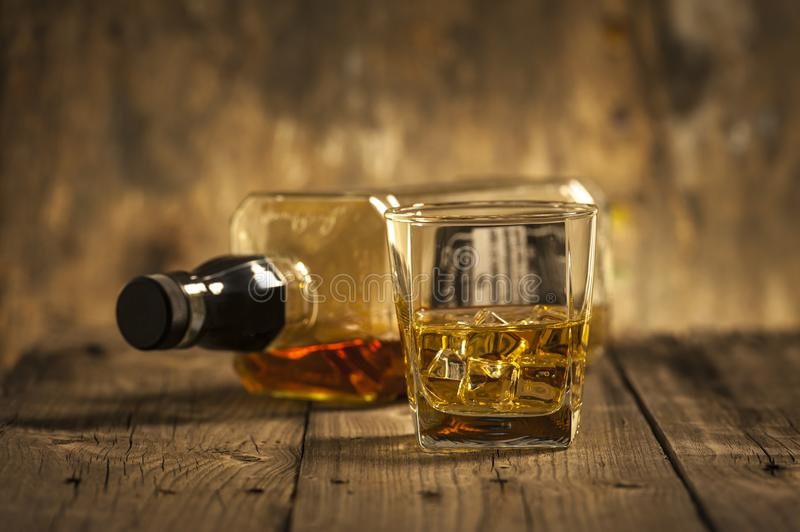 A Glass of whiskey and empty Bottle of whiskey on a wooden background stock images