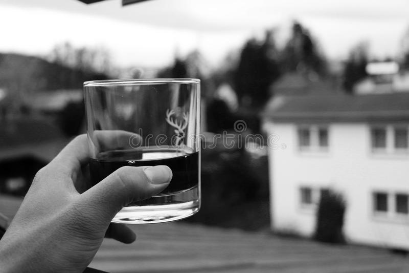 A glass of whiskey in hand and view on countryside. Picture is all in black and white stock images