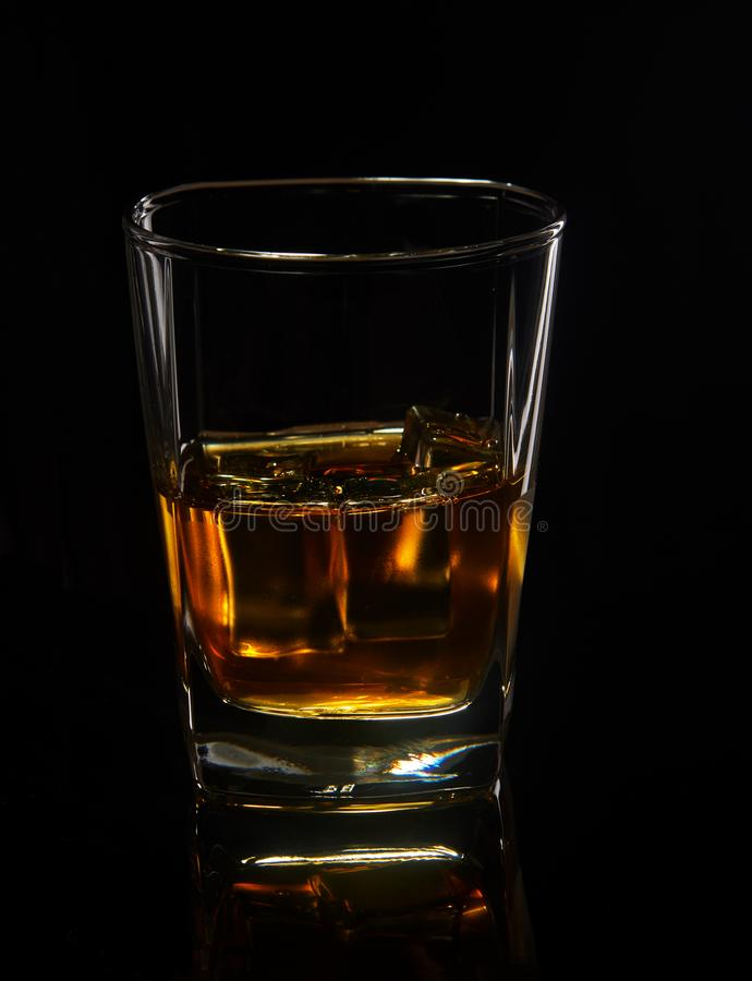 Glass of whiskey with ice on a black background with reflection stock images