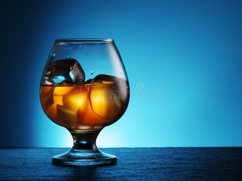 Glass of whiskey with ice on a blue. stock image
