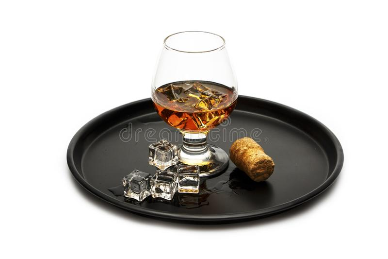 A glass of whiskey with ice or brandy and a square carafe on a black dish isolated against a white background. Whiskey with ice in royalty free stock photo
