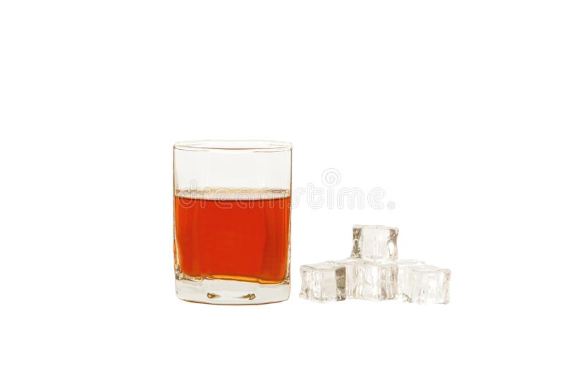 A glass of whiskey with ice or brandy and a square carafe isolated on a white background. Whiskey with ice in a glass a royalty free stock image