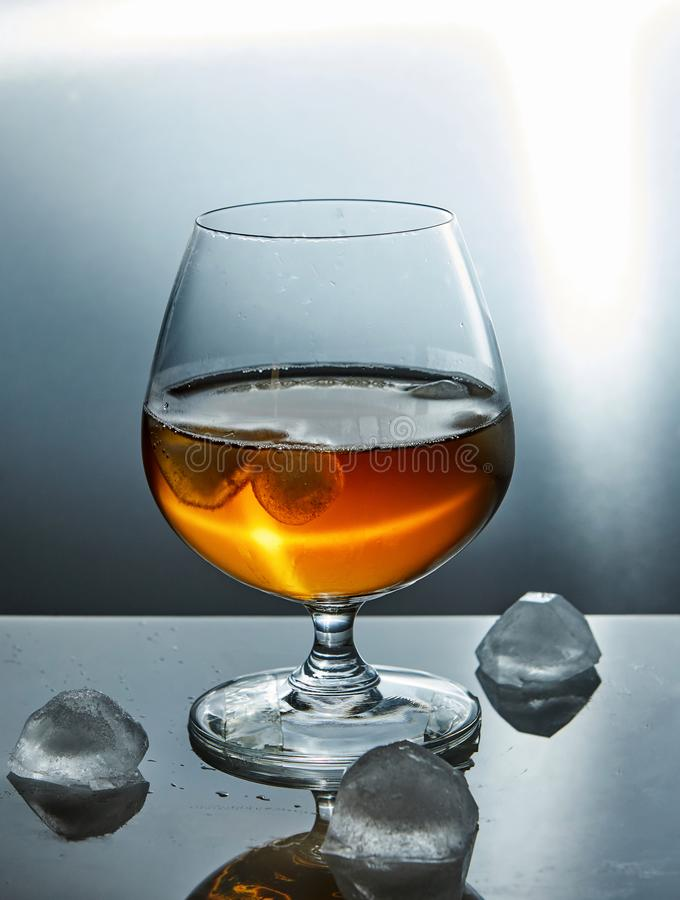 A glass of whiskey with ice royalty free stock photography