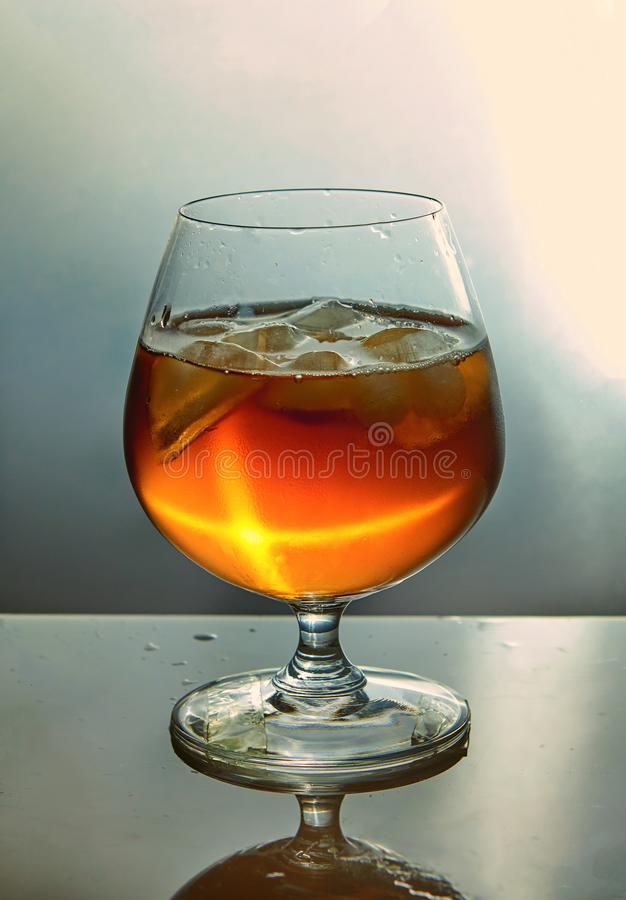 A glass of whiskey with ice royalty free stock image