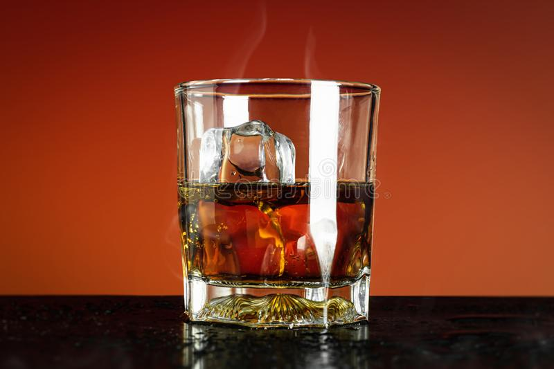 Glass of whiskey and ice cube on red background and cooling smoke. Close Up of whisky glass with alcohol drink. Brandy glass stock photography