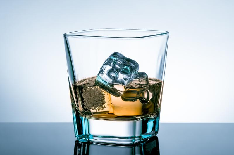 Glass of whiskey with ice cubes on bar table with reflection on light blue tint background stock photos