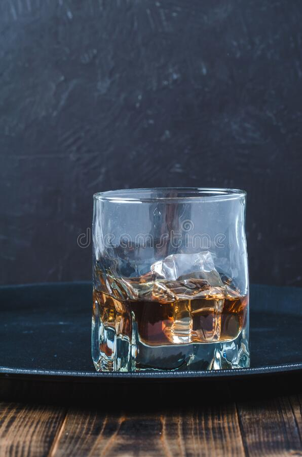 Glass of whiskey with ice cubes on a black tray and wooden table/Glass of whiskey with ice cubes on a black tray and wooden table stock photo