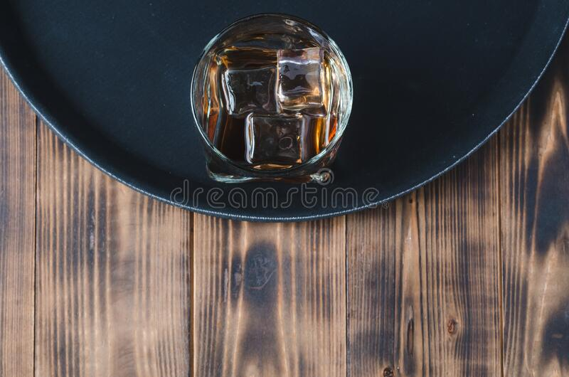 Glass of whiskey with ice cubes on a black tray and wooden table/Glass of whiskey with ice cubes on a black tray and wooden table royalty free stock images