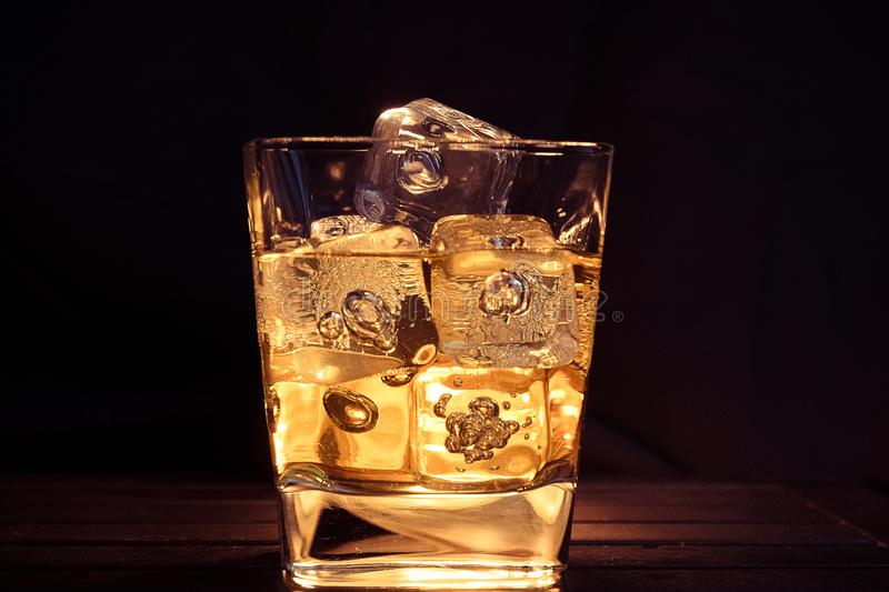 Glass of whiskey with ice cubes on dark background and wood table, relax with whisky concept on the warm atmosphere stock photos