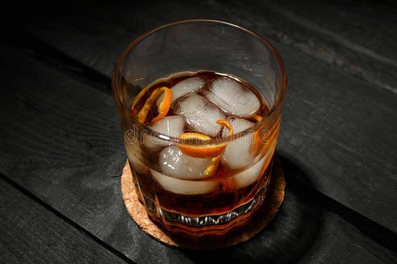 Glass of whiskey with ice cubes on dark wooden background stock photo