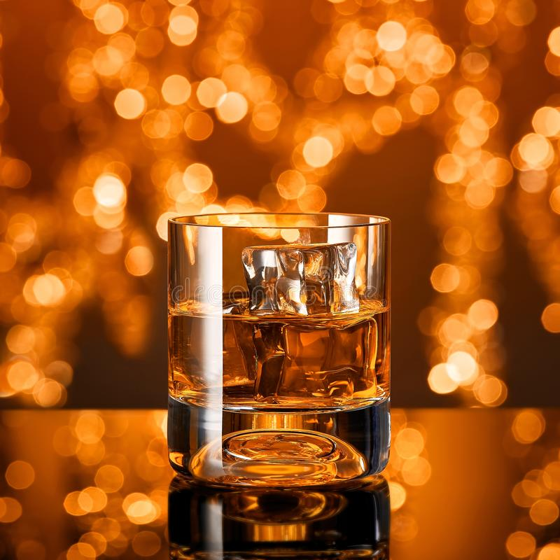 Glass of whiskey with ice cubes in front of christmas lights royalty free stock photography