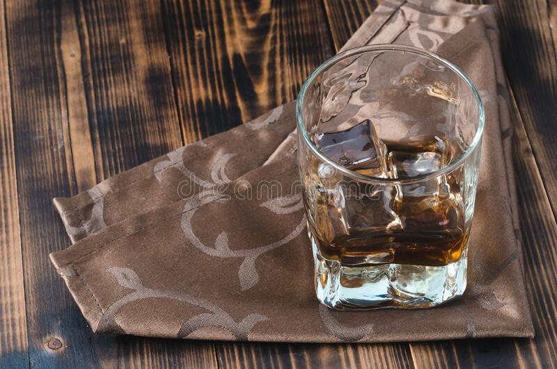 Glass of whiskey and ice cubes on a napkin/Glass of whiskey and ice cubes on a napkin. Wooden table royalty free stock photography