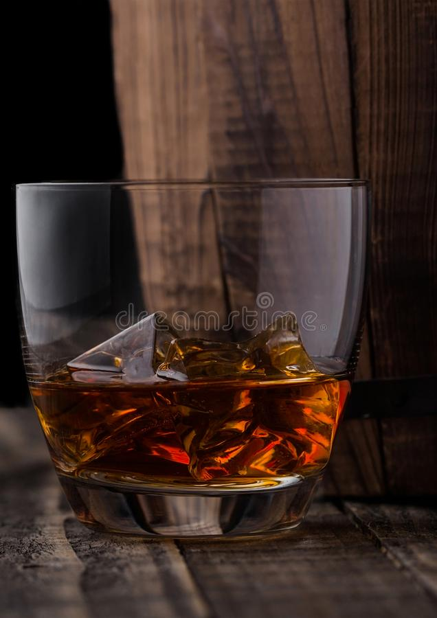 Glass of whiskey with ice cubes next to wooden barrel. Cognac br. Glass of whiskey with ice cubes next to wooden barrel. Cognac and brandy drink royalty free stock image