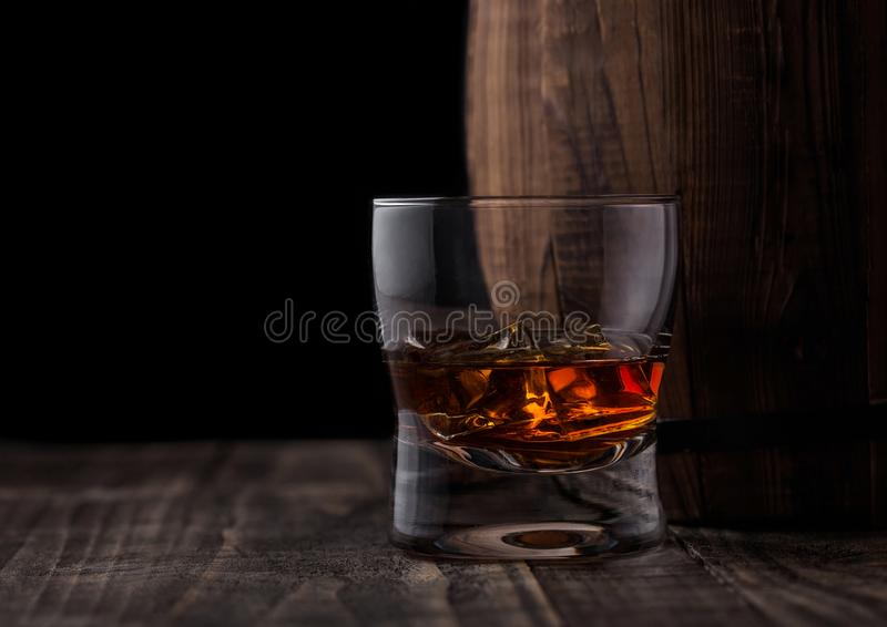 Glass of whiskey with ice cubes next to wooden barrel. Cognac br. Glass of whiskey with ice cubes next to wooden barrel. Cognac and brandy drink royalty free stock photos