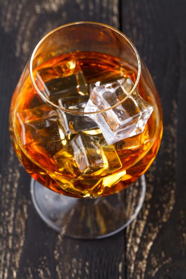 Glass of whiskey with ice cubes served on wooden planks. Vintage countertop with highlight and a glass of hard liquor royalty free stock images
