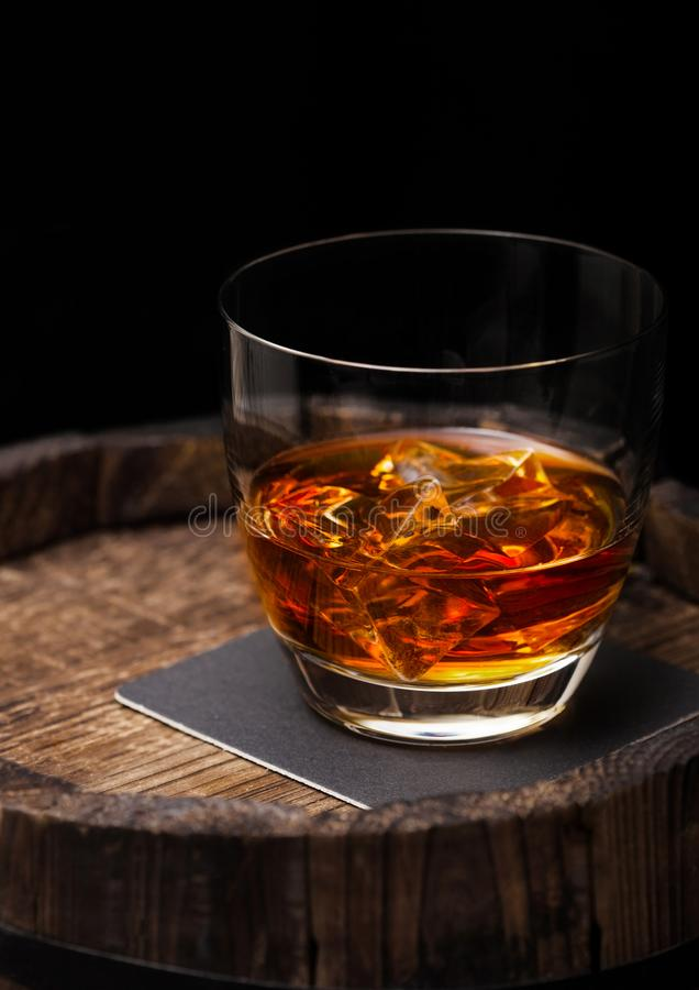 Glass of whiskey with ice cubes on top of wooden barrel. Cognac. And brandy drink royalty free stock photography