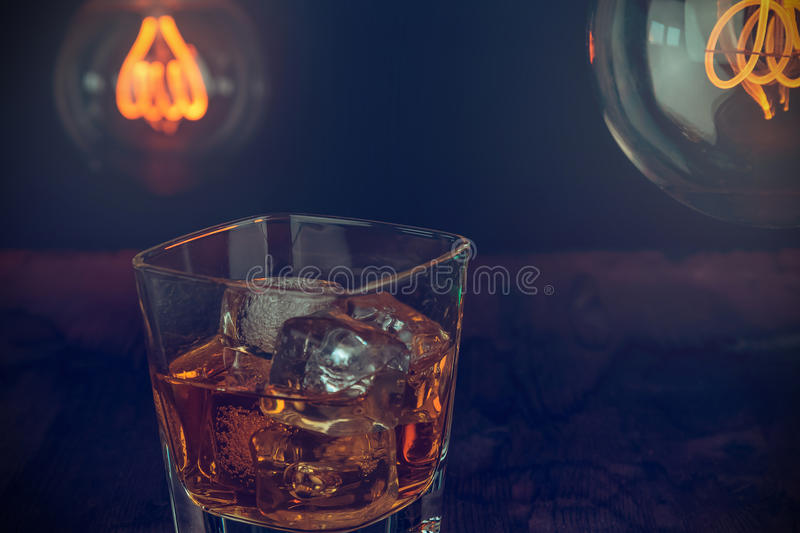 Glass of whiskey with ice cubes on wood table, warm atmosphere, time of relax with whisky with some light warm bulb. On background royalty free stock photo