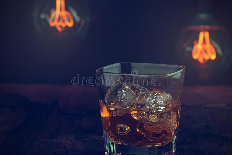 Glass of whiskey with ice cubes on wood table, warm atmosphere, time of relax with whisky with some light warm bulb. On background royalty free stock photos