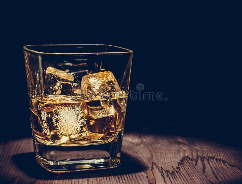 Glass of whiskey with ice cubes on wood table, warm atmosphere, time of relax with whisky. With space for text stock photo
