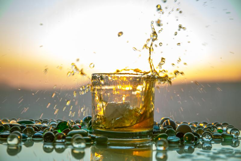 A Glass Of whiskey with ice and gold sunlight. Outdoor shot of whiskey with splash on sunset background royalty free stock photos