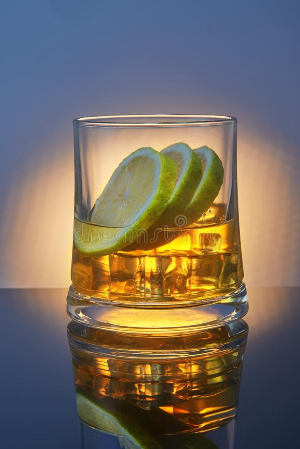 A glass of whiskey with ice and lemon on a blue background with orange backlight and reflection stock photography