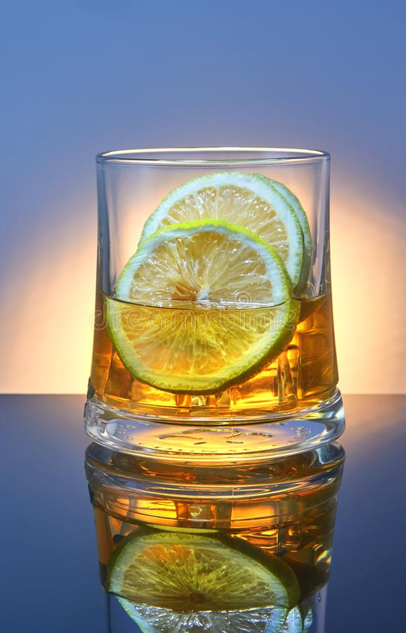 A glass of whiskey with ice and lemon on a blue background with orange backlight and reflection stock image