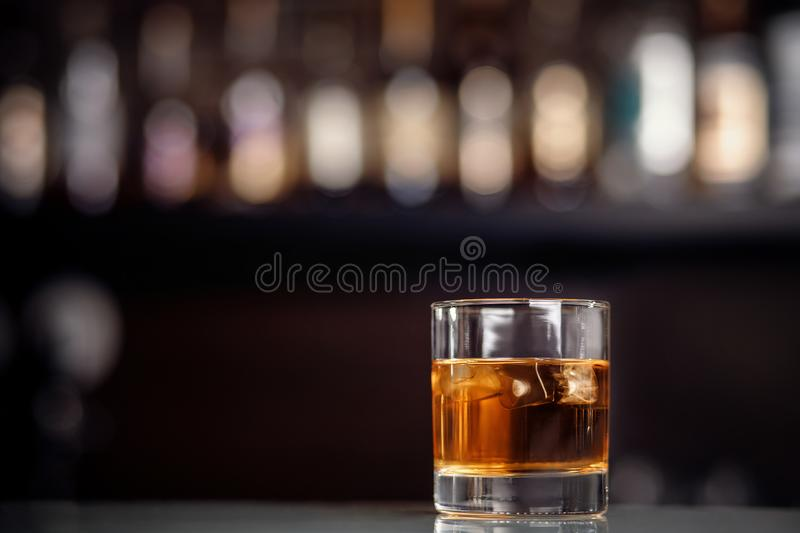 Glass of whiskey with ice stands on bar counter royalty free stock photo