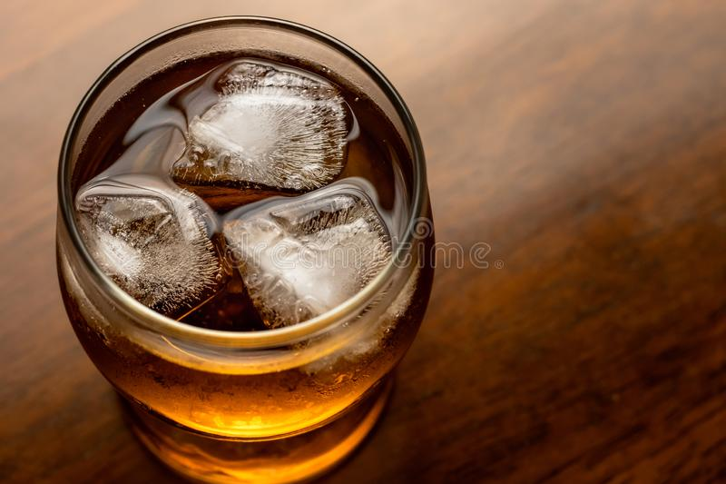 Glass of whiskey with ice on wooden background. Bourbon on dark wood table. Alcohol brown drink with bubbles. Cooled rum, top view stock image