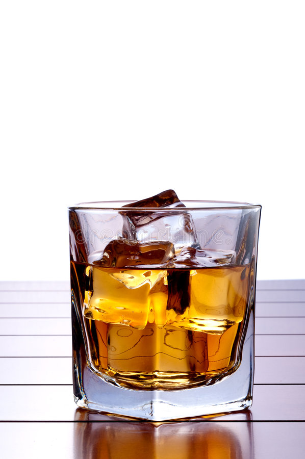 A glass of whiskey with ice on a wooden bar. A vertical image of a glass of whiskey with ice on a wooden bar table with a white background and space for copy stock photos