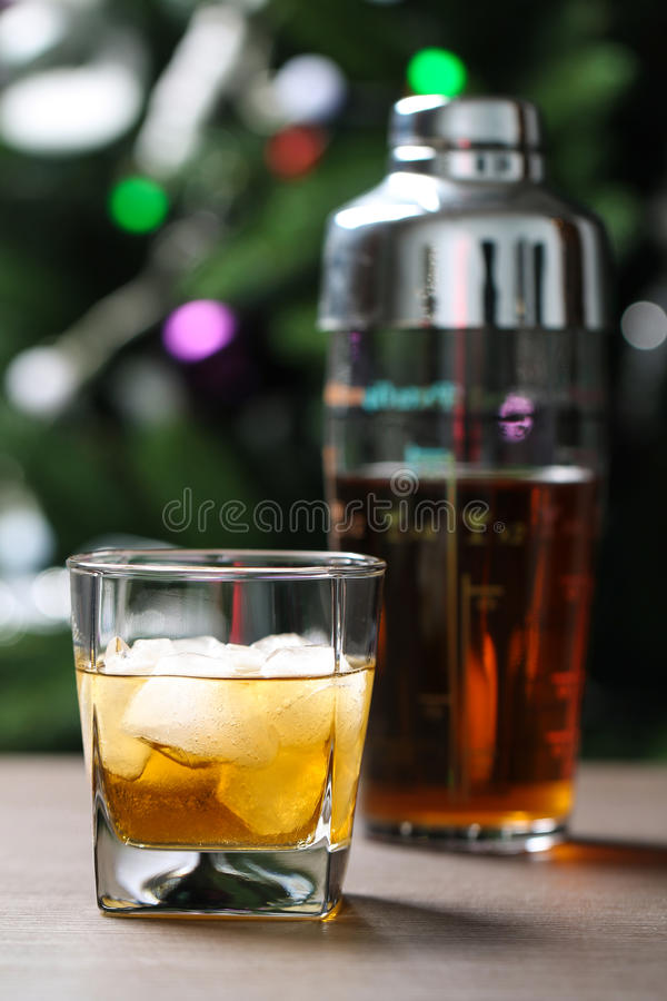 Glass with whiskey and ice on wooden table. On the background of the shaker and trees stock images