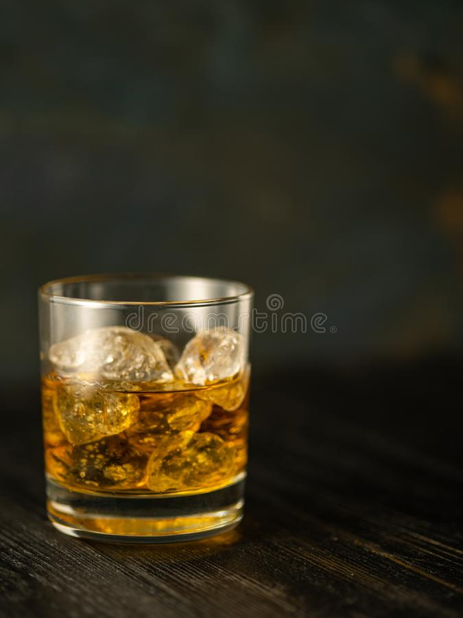 Glass of whiskey with ice on a wooden table. Shallow depth of field. stock photos