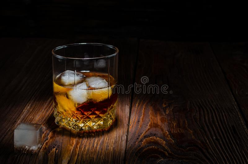 Glass of whiskey with ice on a wooden table stock photos