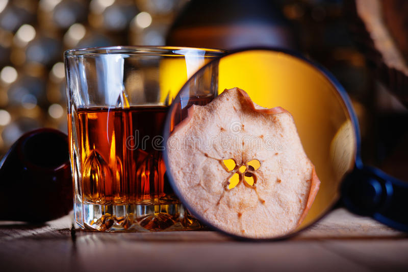 Glass of whiskey, magnifying glass, dried apple and smooking pipe. Glass of whiskey, magnifying glass, dried apple and vintage smooking pipe stock photo