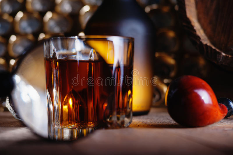 Glass of whiskey, magnifying glass and smooking pipe. Glass of whiskey, magnifying glass and vintage smooking pipe royalty free stock photography